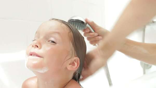 Mother washes daughters hair in bath using shower attachment. Royalty-free stock video