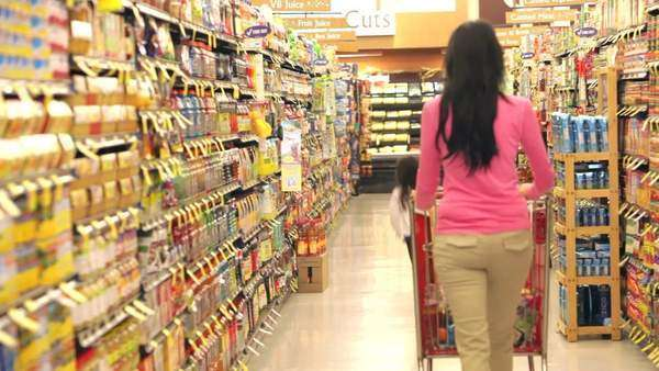 Daughter runs down supermarket aisle before taking packet from shelf and putting into trolley. Royalty-free stock video