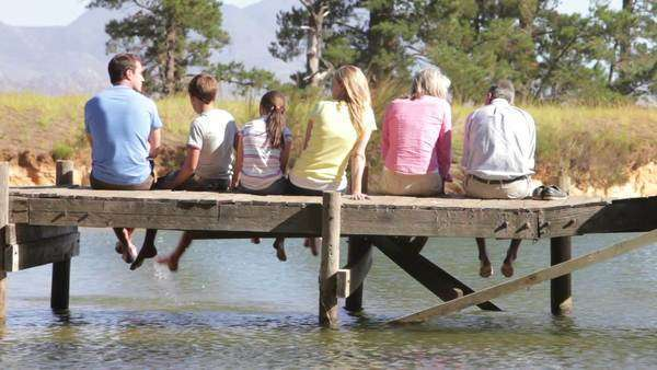 Rear view of multi-generation family sitting in on wooden jetty at edge of lake. Royalty-free stock video