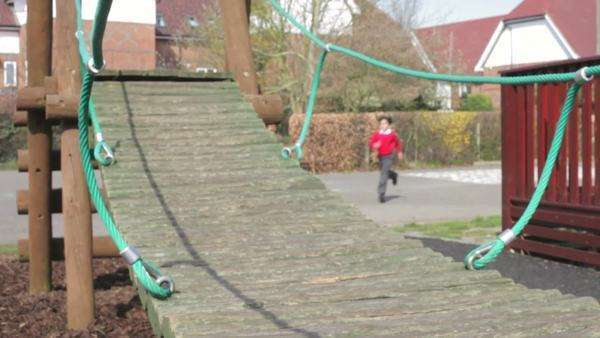Three schoolboys run across playground and over climbing equipment. Royalty-free stock video
