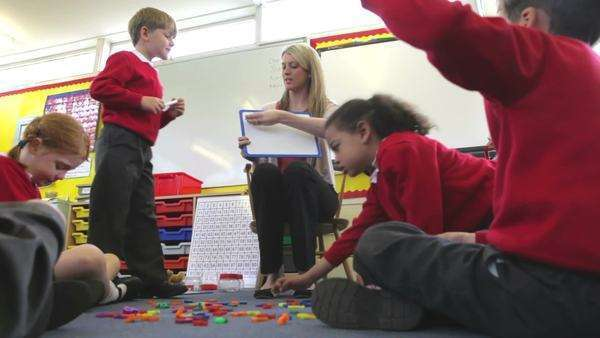 Pupils playing with plastic letters as teacher holds magnetic board. Royalty-free stock video
