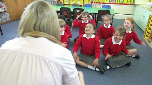 View from behind teacher as children sing song and copy actions. Royalty-free stock video