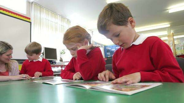 Children reading books at desk with teacher helping female pupil. Royalty-free stock video