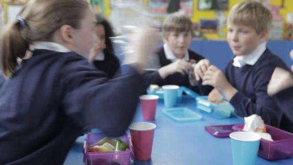 Camera tracks across table as pupils enjoy packed lunch. Royalty-free stock video
