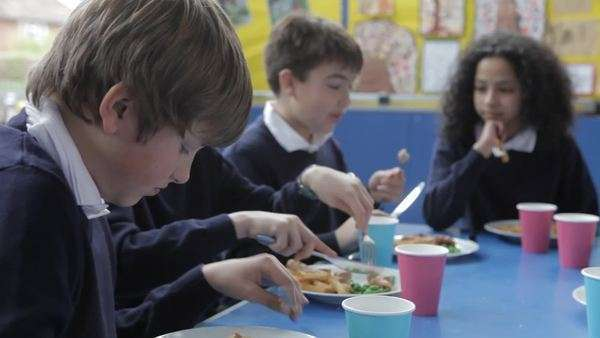 Camera tracks across table as pupils enjoy lunch. Royalty-free stock video