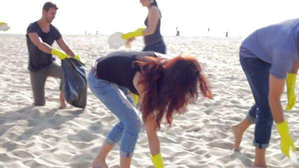 Camera follows group of young people as they clear rubbish from beach and put it into bags. Royalty-free stock video