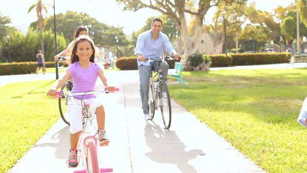 Children with parents cycling through park. Royalty-free stock video