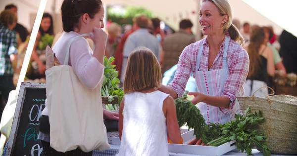 Mother and daughter buying vegetables at a market stall Royalty-free stock video