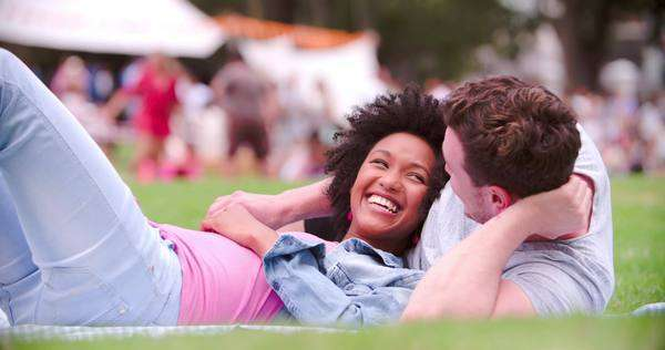 Couple relaxing on the grass at an outdoor event Royalty-free stock video