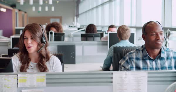 Male and female call centre workers wearing headsets Royalty-free stock video