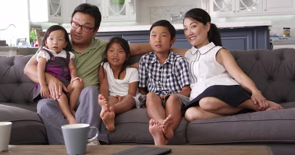 Family sitting on sofa at home watching TV Royalty-free stock video