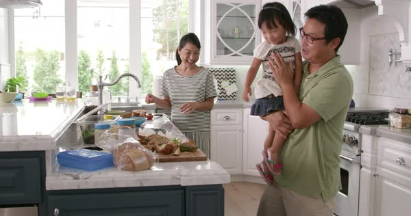 Parents prepare food as children play in kitchen Royalty-free stock video