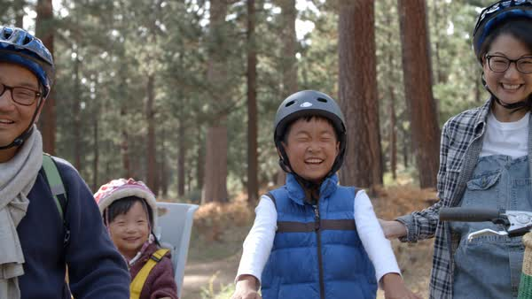 Handheld pan of family on bikes in a forest, close up Royalty-free stock video