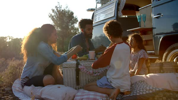 Family eating picnic outside their camper van at sundown Royalty-free stock video