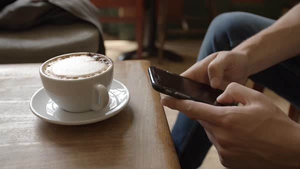 Young man in cafe messaging with smartphone, close up detail Royalty-free stock video