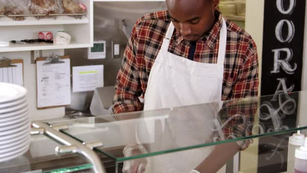 Man slicing bread behind the counter of a sandwich bar, shot on R3D Royalty-free stock video