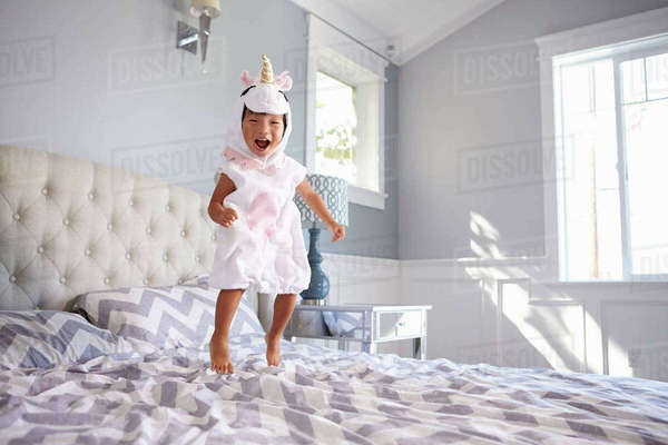 Girl Dressed In Unicorn Costume Jumping On Bed At Home Royalty-free stock photo
