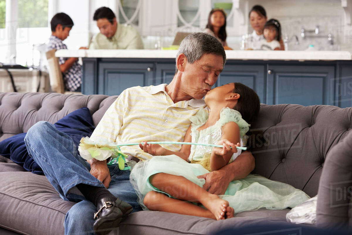 Grandfather And Granddaughter Relaxing On Sofa At Home Royalty-free stock photo