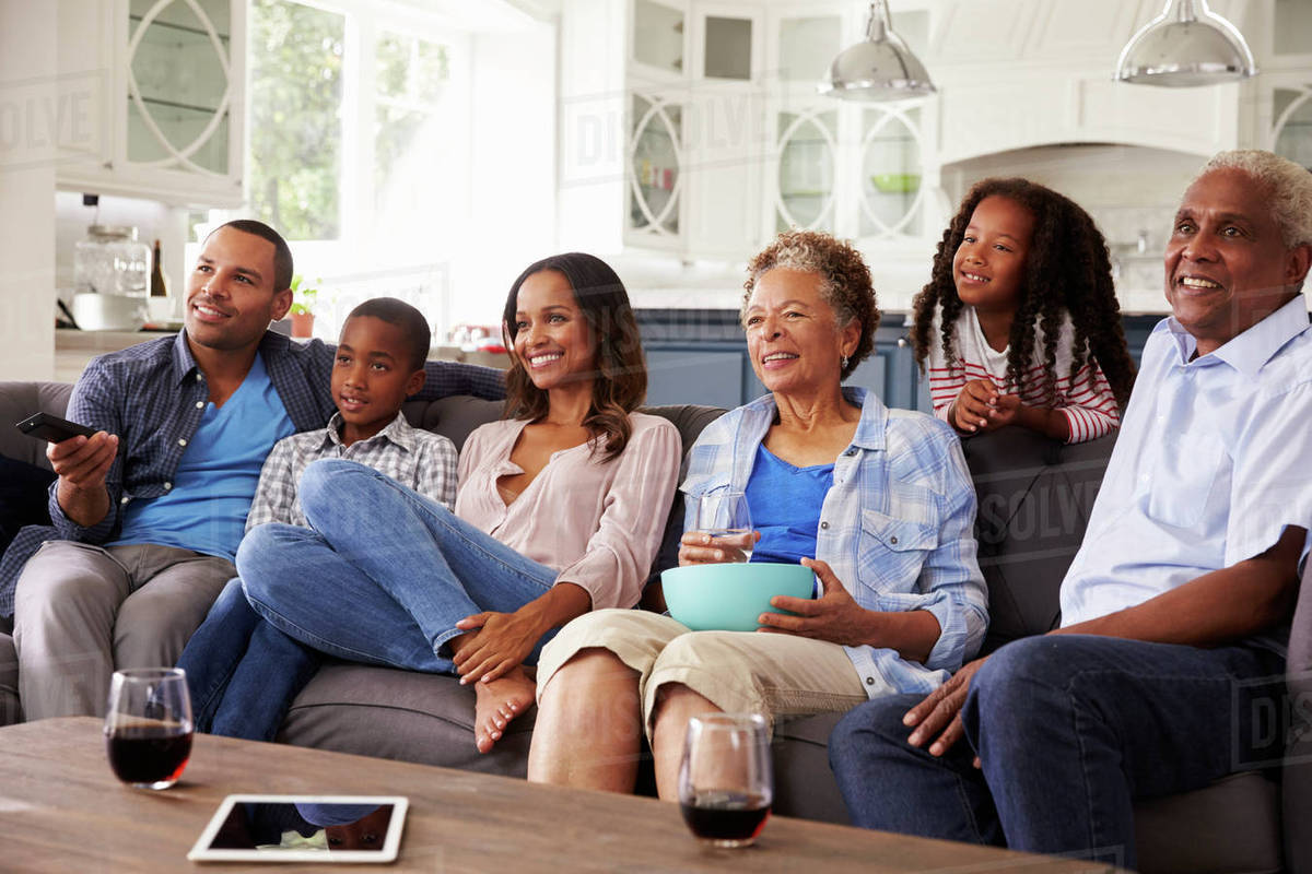 multi generation black family watching movie on tv