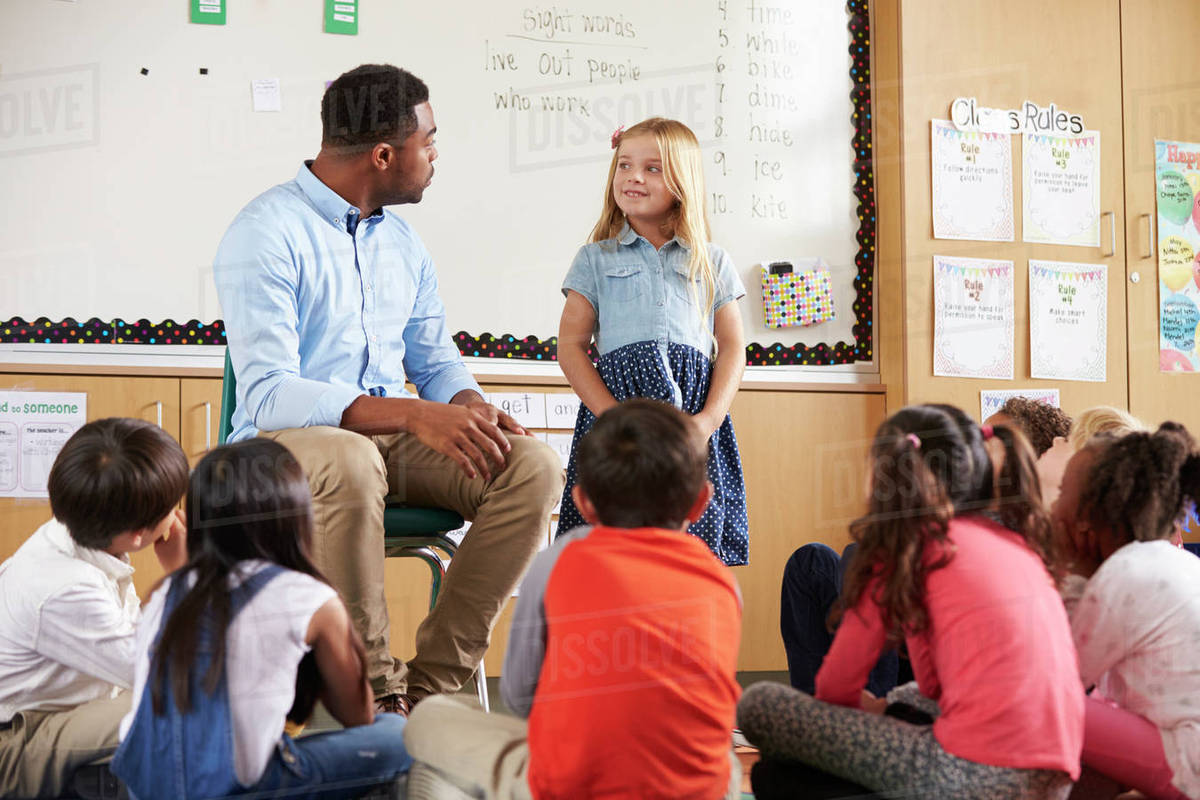 Schoolgirl At Front Of Elementary Class With Teacher