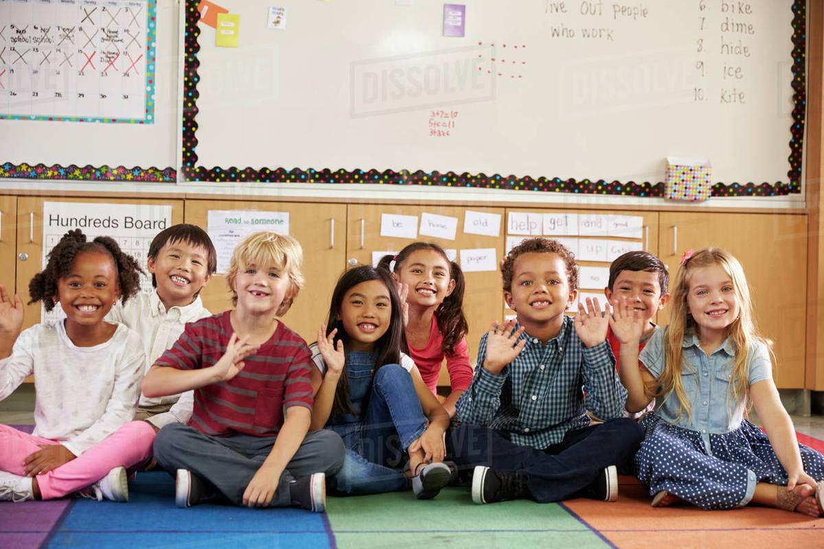elementary school kids sitting on classroom floor stock photo