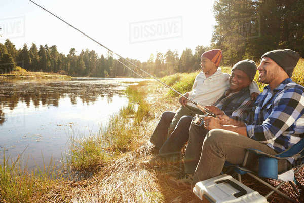 Grandson With Father And Grandfather Fishing By Lake Royalty-free stock photo
