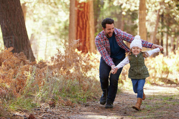 Father And Daughter Running Through Fall Woodland Royalty-free stock photo