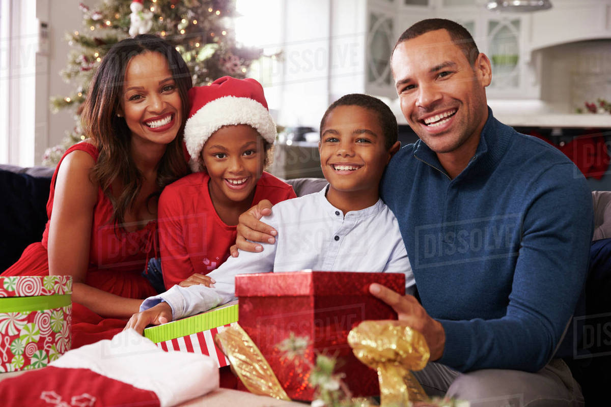 family opening christmas presents at home together