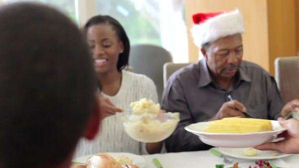 Multi-generation table sitting around kitchen table enjoying christmas meal together. Royalty-free stock video