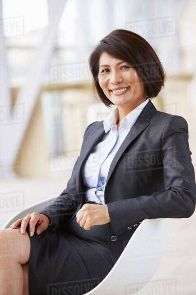 Vertical portrait of smiling Asian businesswoman, sitting Royalty-free stock photo