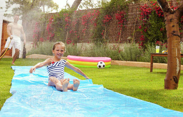 Father And Daughter Having Fun On Water Slide In Garden Royalty-free stock photo