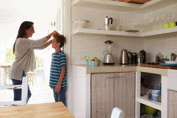 Mother Measuring Son's Height Against Wall Royalty-free stock photo