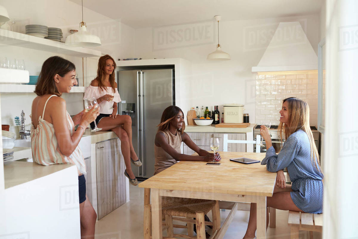 Four Women Drinking Wine In Kitchen During A Girls Night In Stock Photo