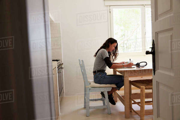 View from doorway of teenage girl doing homework in kitchen Royalty-free stock photo
