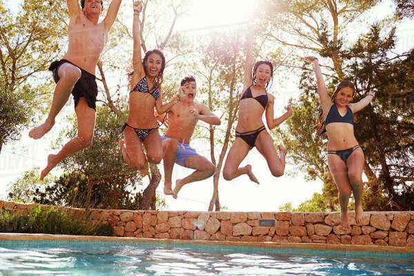 Teenagers jumping into an outdoor pool look to camera, Ibiza Royalty-free stock photo