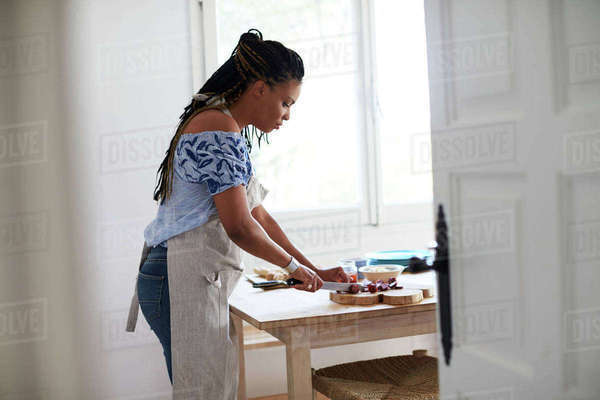 View from doorway of woman chopping food on kitchen table Royalty-free stock photo