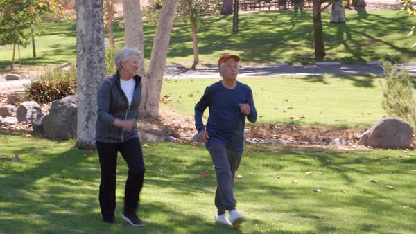 Senior couple power walking through park in slow motion Royalty-free stock video