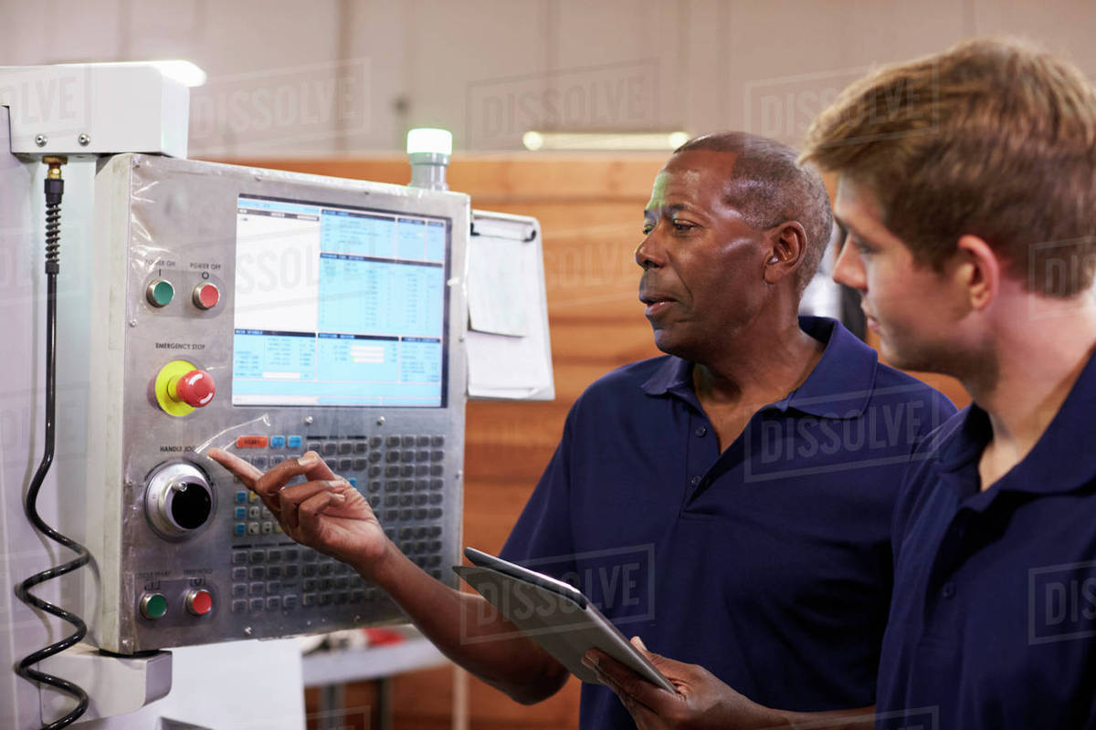 Engineer training male apprentice on CNC machine stock photo