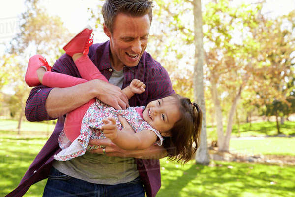 Dad cradling toddler daughter in his arms at the park Royalty-free stock photo