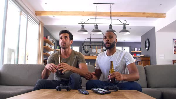 Two male friends sit on sofa and watch sports on television Royalty-free stock video
