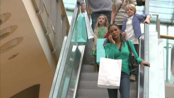 Woman coming down escalator in shopping mall talking on mobile phone. Royalty-free stock video