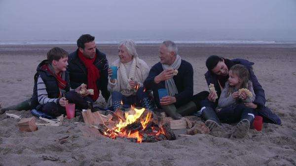 Multi generation family gathered around fire on beach cooking hot dogs in slow motion. Royalty-free stock video
