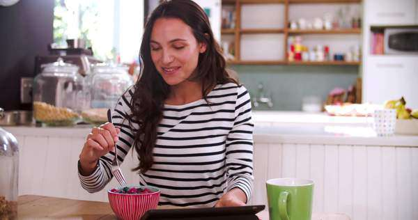 Young woman sits at table in kitchen eating breakfast whilst using digital tablet - male partner gets ready in background. Royalty-free stock video