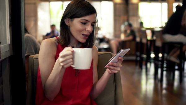 Young woman with smartphone drinking coffee in cafe Royalty-free stock video