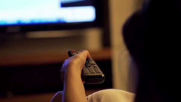 Woman watching TV at night and changing channels with remote Royalty-free stock video