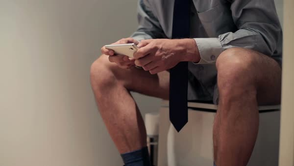 Businessman with smartphone sitting on toilet Royalty-free stock video