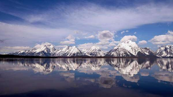 Timelapse showing water surface reflecting snowy mountain peaks Rights-managed stock video
