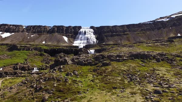 Drone shot of waterfall and landscape, blue sky in background Royalty-free stock video
