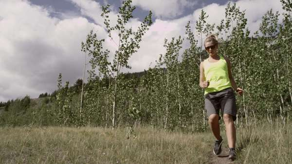 Wide shot of woman running in nature Royalty-free stock video