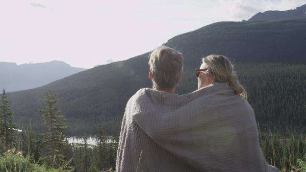 Medium shot of a couple wrapped under a blanket in the mountains Royalty-free stock video